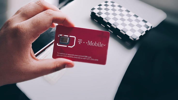 Para Cego Ver: na imagem, uma mão, segurando um cartão rosa com chip de internet da marca parceira e ao fundo a mesa da aeronave e uma carteira xadrez