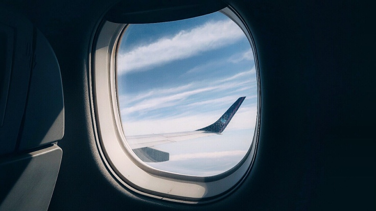 Para Cego Ver: na imagem, a janela da aeronave com uma pequena parte da asa aparecendo no fundo do céu