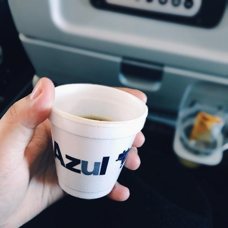 Para Cego Ver: na imagem, uma mão com um copo de café da companhia aérea AZUL e ao fundo, o banco da aeronave
