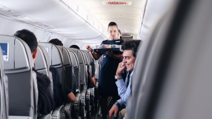 Para Cego Ver: na imagem, há a parte interna de uma aeronave, com uma comissária de bordo segurando uma bandeja com copos de suco e nacks, e um homem (passageiro) sorrindo