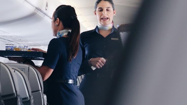 Na Imagem: Duas comissárias de Bordo da Companhia Azul, prestando atendimento aos passageiros.