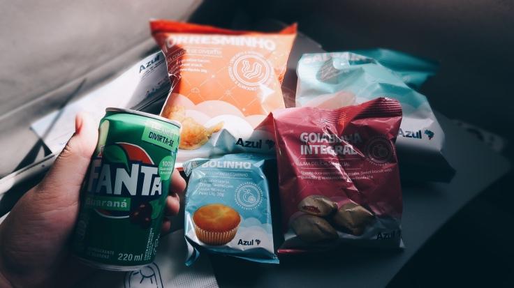 Para Cego Ver: na imagem, vários pacotes de snacks de marcas variadas e bem coloridos, com um refrigerante em lada, sobre a mesa da aeronave